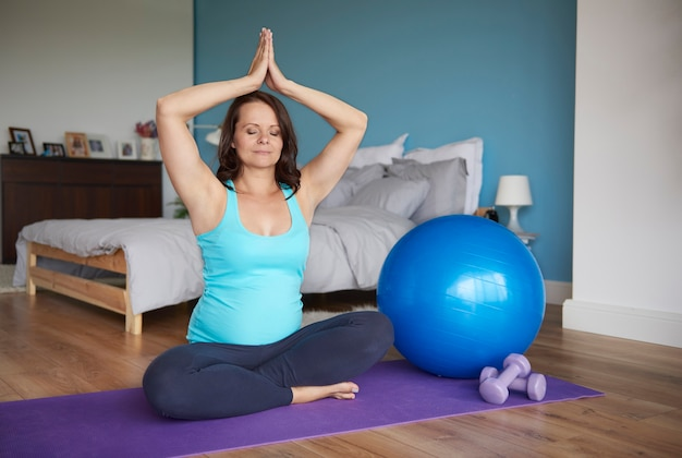 Беременная женщина сосредоточилась на упражнениях йоги