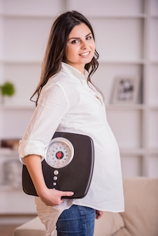 Pregnant adult woman holding scales at home.
