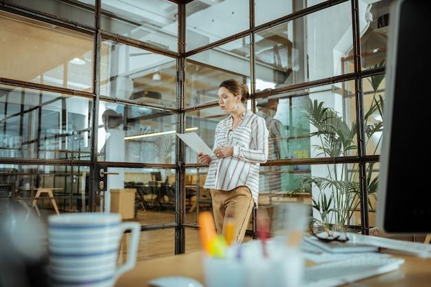 Беременная и работающая. беременная работающая преуспевающая женщина в белой блузке усердно работает