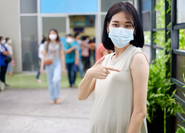 A pregnant asian mother in a long gown is standing holding her stomach and showing plaster after receiving the vaccination.