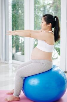 아침에 집에서 피트니스 공에 운동을 하 고 임신 아시아 여자