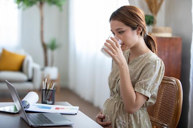 임신한 아시아 여성이 우유를 마시고 집에서 일하기 위해 노트북을 사용합니다.