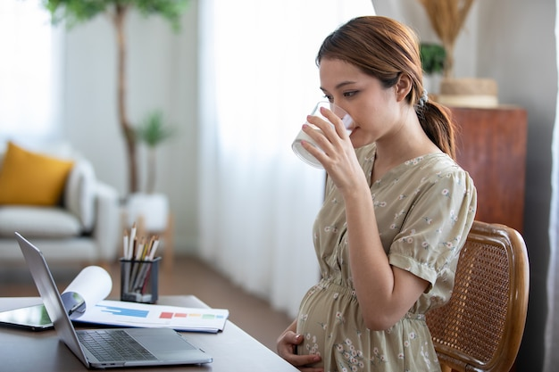 Pregnant asian woman drinking milk and using the laptop for working from home