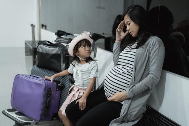 Беременная азиатка чувствует головокружение и его дочь, когда в зале ожидания аэропорта