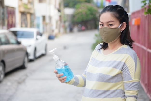 妊娠中のアジアの女性を保持している青いエチルアルコールハンドゲルとカメラ、covid-19コンセプトを見て