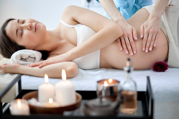 Pregnant asian woman lying on bed, having relaxing oriental prenatal massage on belly