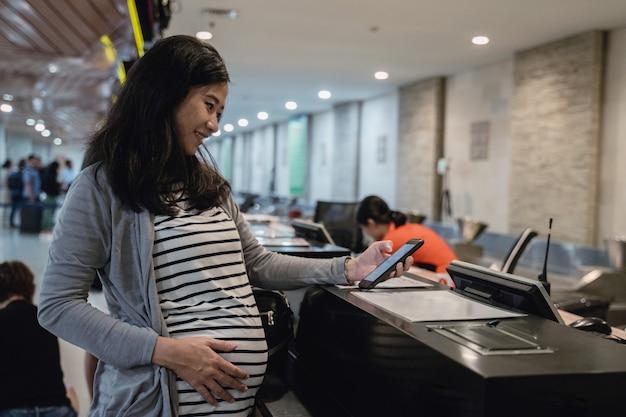 妊娠中のアジアの女性がチケット確認にスマートフォンを使用