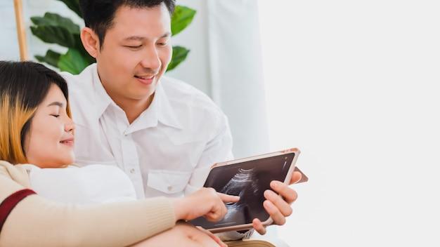 ソファに座ってタブレットを使用して夫と超音波画像を見る妊娠中のアジアの女性の妻