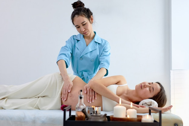 Беременная азиатская молодая женщина, лежа на кровати и имеющая расслабляющий восточный пренатальный массаж живота, наслаждаясь профессиональным массажем, готовясь к родам, тренируя мышцы