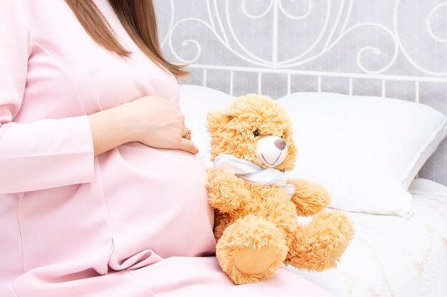 Pregnant beautiful girl is sitting on the bed and her hands.