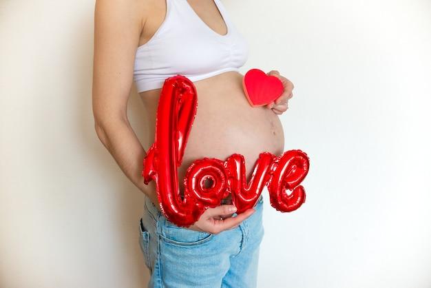 明るい背景に風船の愛と赤いハートの妊娠中の腹。コピースペース