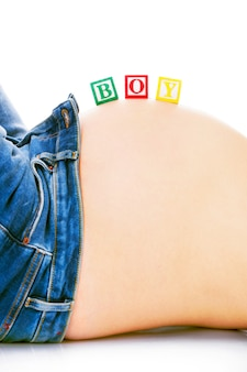 A pregnant belly with wooden blocks on it creating a boy inscription over white background