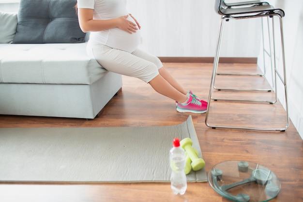 임신 한 검은 머리 여자는 소파를 사용하여 집에서 운동을