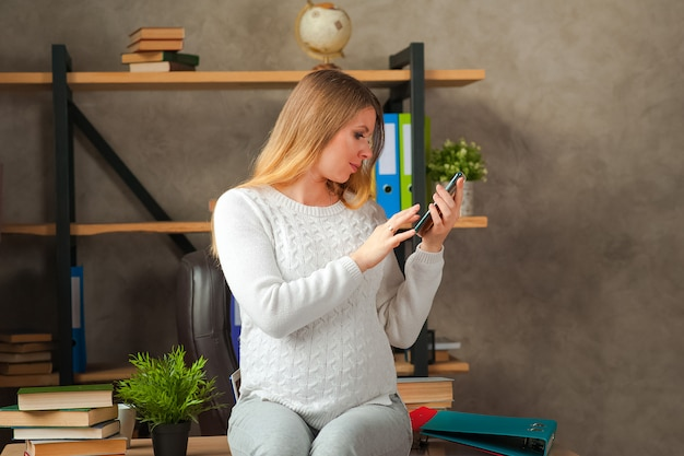 Pregnant blogger takes selfie on the phone. pregnant freelancer in the office with the phone.