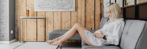 회색 소파에서 휴식을 취하는 임신한 금발의 여자