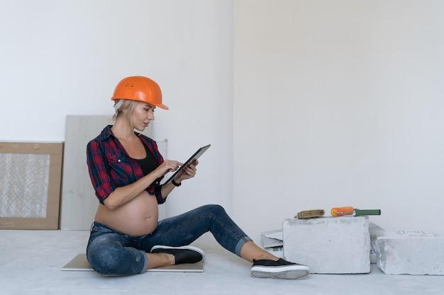 Беременная блондинка сидит на полу в комнате, где ведутся ремонтные работы. на голову надевается защитный шлем. держит планшет в руках просматривает видео в соцсетях