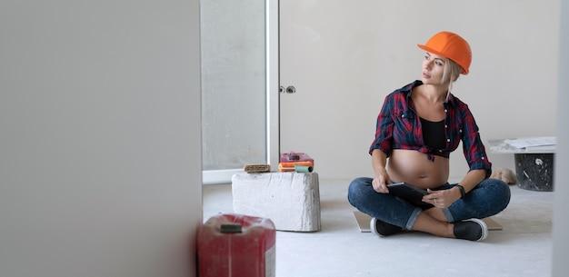 Беременная блондинка сидит на полу в комнате, где ведутся ремонтные работы. на голову надевается защитный шлем. глядя. скопируйте пространство.