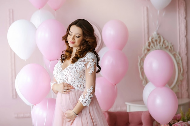 Pregnant bride with long hair on a background of pink-white balloons