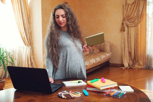 랩톱을 사용하고 집에서 일하는 임신한 비즈니스 여성. 온라인 쇼핑을 하는 여자. 임신, 작업 및 쇼핑 개념입니다. 집에서 온라인으로 공부하는 임산부.
