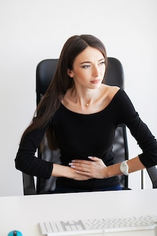 Pregnant business woman working at office motherhood sitting tired