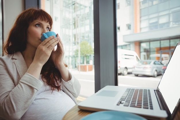 Pregnant businesswoman having coffee in cafeteria