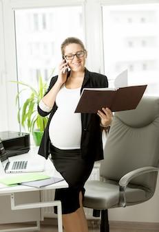 휴대 전화를 사용하여 검은 양복에 임신 한 사업가