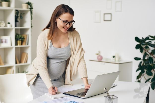 机の上に曲がって、オフィスでネットサーフィンしながらノートパソコンのディスプレイを見ているスマートカジュアルウェアの妊娠中の実業家