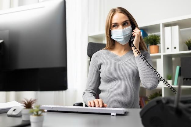 Беременная бизнесвумен разговаривает по телефону за своим офисным столом в медицинской маске