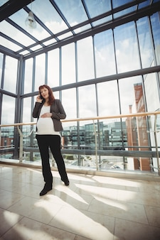 Pregnant businesswoman talking on mobile phone near corridor