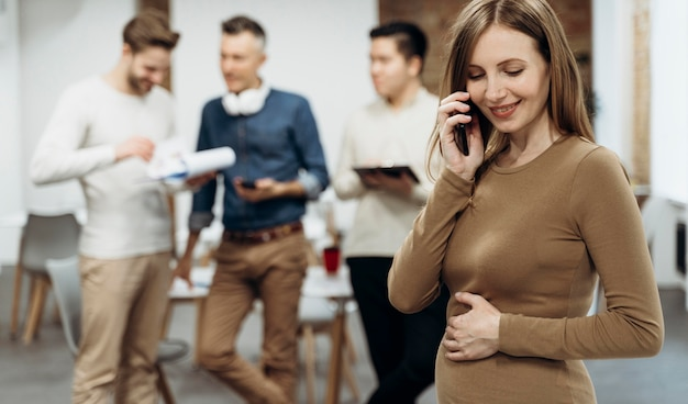 Pregnant businesswoman talking on the phone while touching her belly