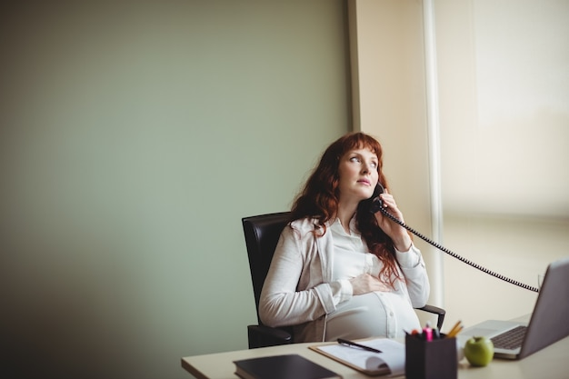 Беременная бизнесвумен трогает живот во время разговора по телефону