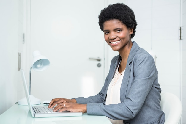 Pregnant businesswoman using laptop in the office