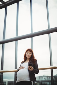 Pregnant businesswoman using mobile phone near corridor