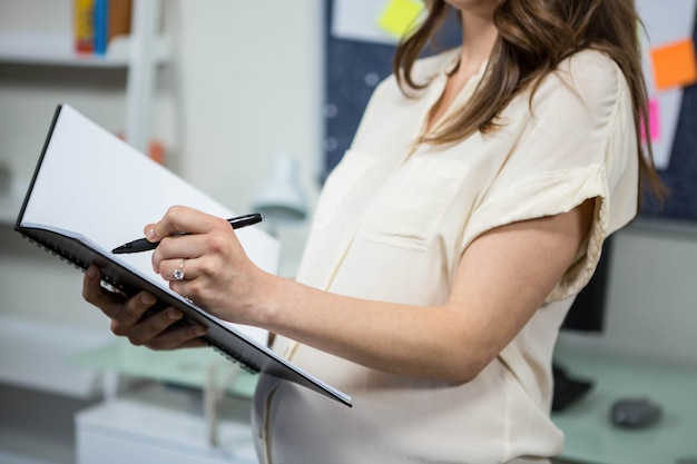 Pregnant businesswoman writing in folder in home office