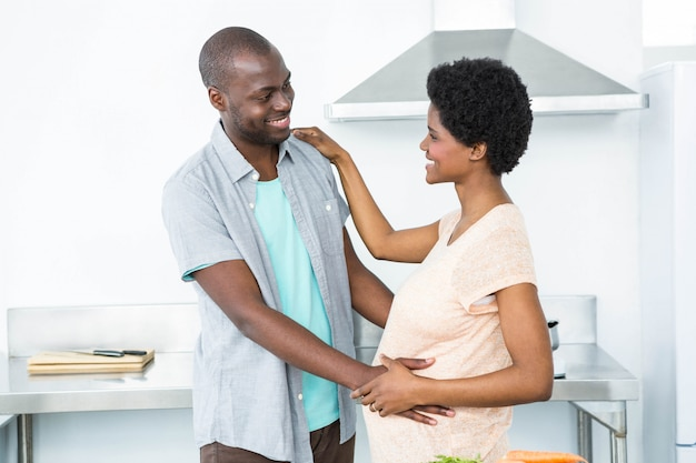 Pregnant couple cuddling each other in kitchen at home