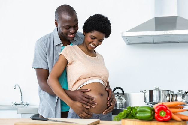 Pregnant couple embracing each other in kitchen at home