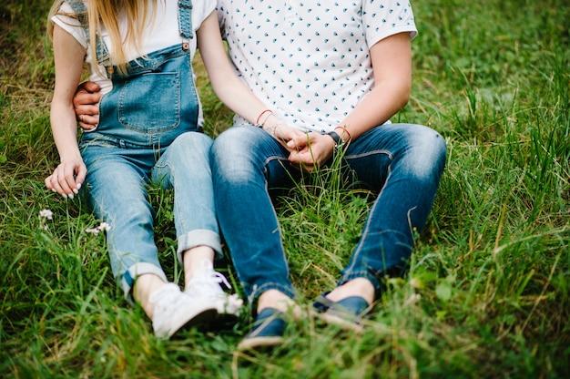 임신 부부는 정원 배경에서 야외에서 잔디에 앉아 뱃속에 손을 잡으십시오.