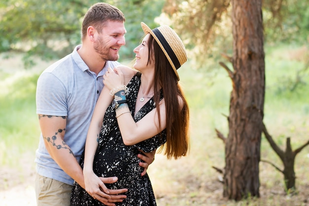 Pregnant couple hugging in the park in warm sunny day