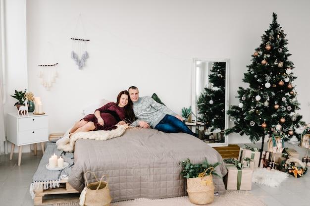 Беременная влюбленная пара, лежа на кровати возле елки