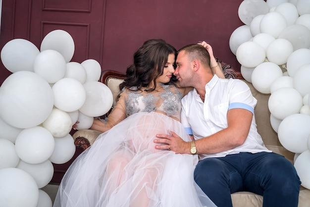 Беременная пара в студии, сидя на диване и целуя