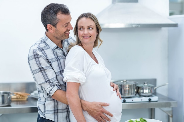 Pregnant couple looking at camera in kitchen
