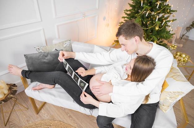 腹の中で超音波写真の赤ちゃんを探している妊娠中のカップル。リビングルームのソファに横になっている子供を世話している間、ママとパパは幸せを感じています。