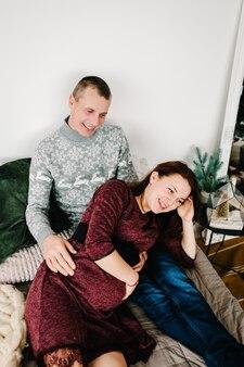 Беременная пара, лежа возле елки с новым годом и рождеством