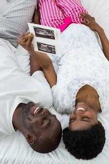 妊娠中のカップルがベッドに横になっていると超音波スキャンを見て