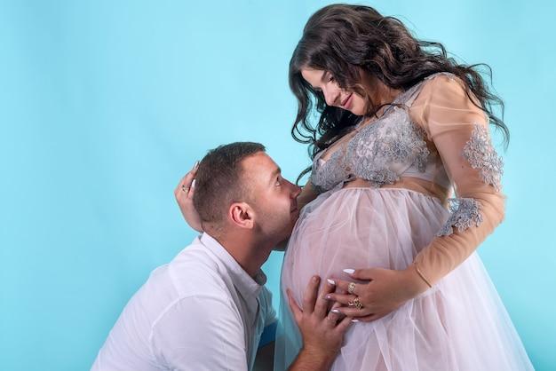 임신한 커플입니다. 뱃속에 그의 아름다운 아내에게 키스하는 남자. 아기를 기다리는 중