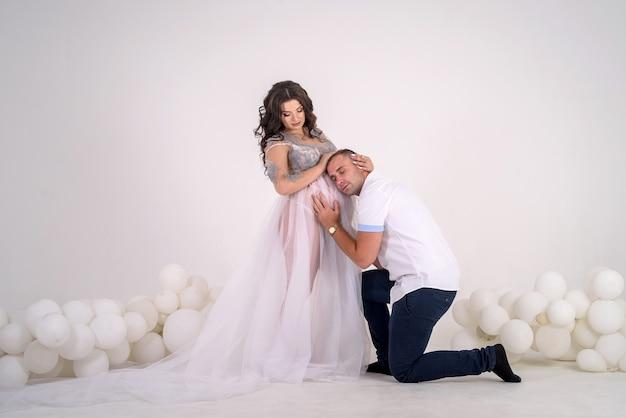 임신 커플. 배꼽에 그의 아름다운 아내를 키스하는 남자. 아기를 기다리고