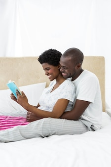 Pregnant couple reading a book on bed at home