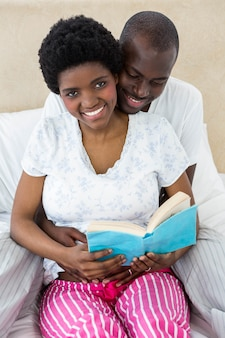 Pregnant couple reading a book at home