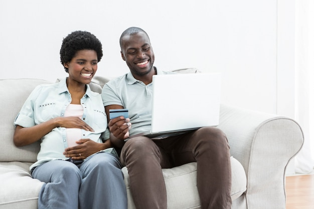 Pregnant couple shopping online on laptop at home