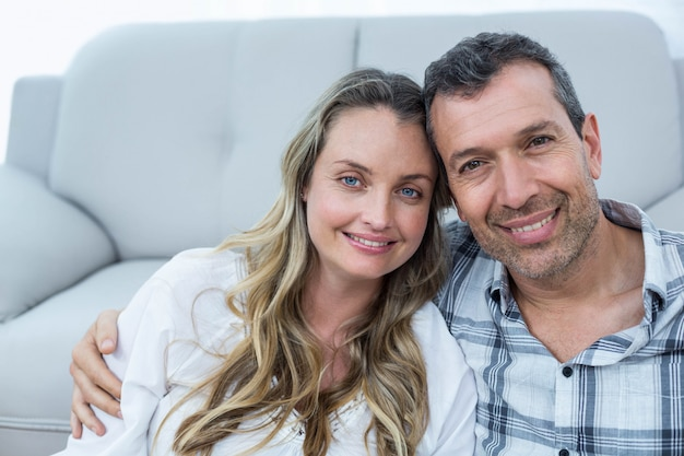 Pregnant couple sitting on floor in living room